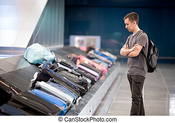 Young man waiting for baggage - Young handsome man passenger...