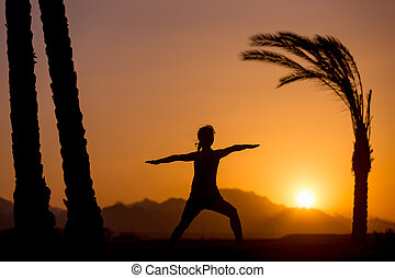 Yoga training in tropical location - Silhouette of young...