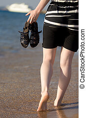 Walking barefoot through the surf - Young woman walking...