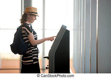 Woman doing self-check-in in airport - Young woman at self...