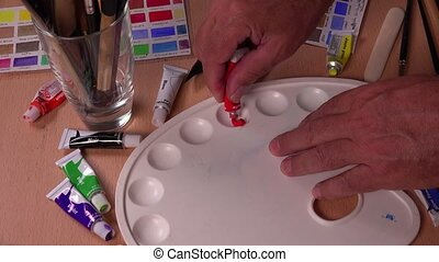 the artist mixes two colors - Red and yellow gouache tubes...
