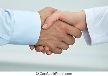 Female medicine doctor shaking hands with male patient...