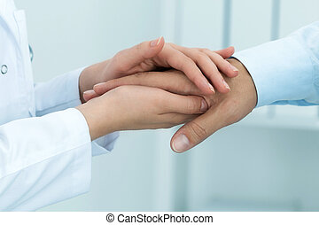 Female medicine doctor reassuring her patient. Hands...