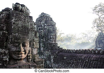 Smiling faces of the king Jayavarman VII in the Temple of...