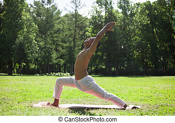 Crescent yoga pose in park - Profile of sporty Indian young...