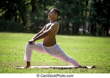 High lunge pose in park - Profile of sporty Indian young man...