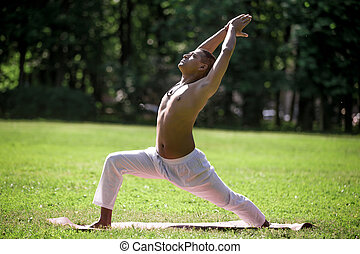 Warrior 1 yoga pose in park - Profile of sporty Indian young...