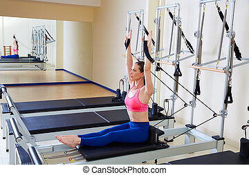 Pilates reformer woman rowing row exercise workout at gym...