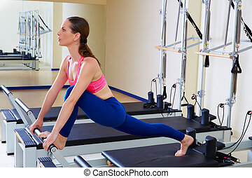 Pilates reformer woman front split exercise workout at gym...
