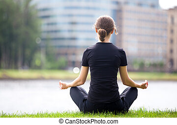 Sukhasana yoga pose - Young woman sitting cross legged on...