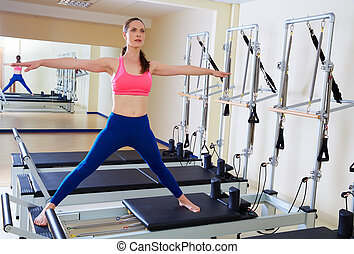 Pilates reformer woman side split exercise workout at gym...