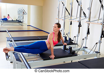 Pilates reformer woman snake twist exercise workout at gym...