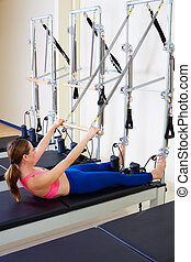 Pilates reformer woman roll up exercise workout at gym...