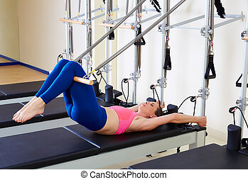 Pilates reformer woman short spine exercise workout at gym...