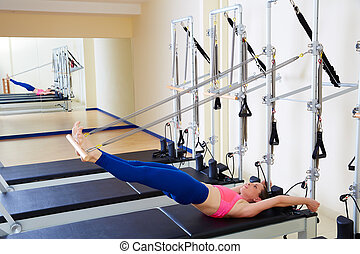 Pilates reformer woman long spine exercise workout at gym...