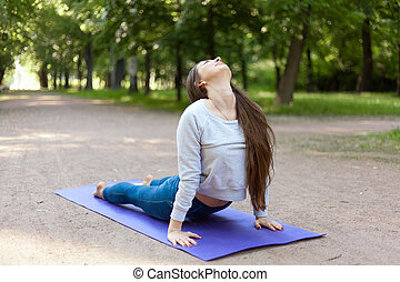Upward facing dog pose in park alley - Beautiful sporty...