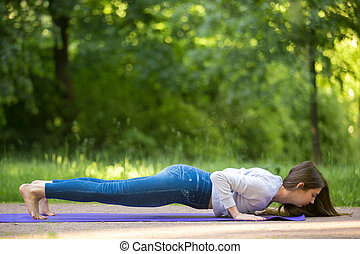 Chaturanga dandasana yoga pose in park alley - Beautiful...