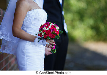 Bridal bouquet in a hands of bride standing with her groom