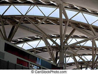 Curved reinforced steel roof joists in a modern airport with glass panes in between.