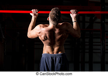 Exercising on chin-up bar - Young attractive caucasian...