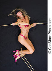 Bondage on the bed - Woman in lingerie and high-heeled shoes...
