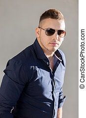 Portrait of good looking guy in sunglasses