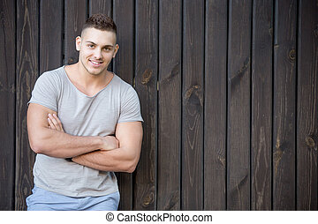 Smiling young man portrait in front of wooden wall -...