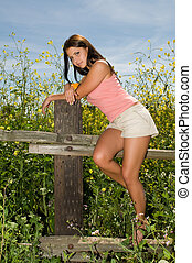 Brunette - Beautiful young brunette leaning on a wooden...