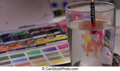 watercolor brush dipped in water - painting creates a...
