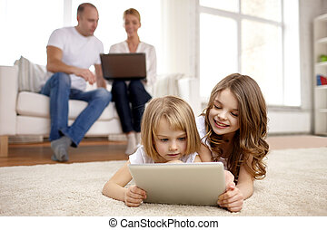 happy little girls with tablet pc computer at home - people,...