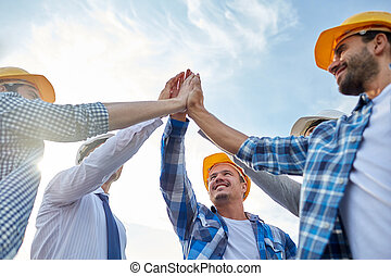 close up of builders in hardhats making high five -...