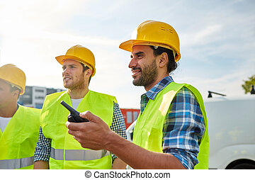 happy male builders in vests with walkie talkie - industry,...