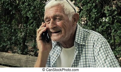 senior man talking at mobile phone - portrait of a senior...