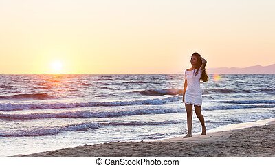 Beautiful young teenager with a white dress on the beach at sunset