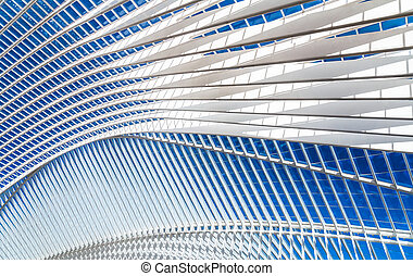 Transparent ceiling in modern railway station with blue sky