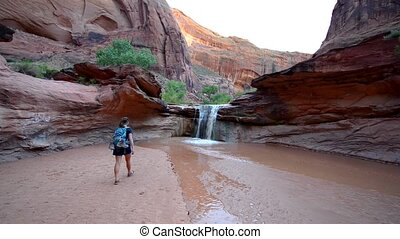 Girl Hiker walking towards the waterfall Coyote Gulch...