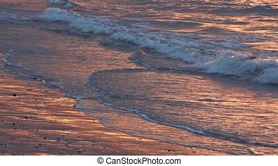 Seascape of waves breaking to shore during sunset abstract...