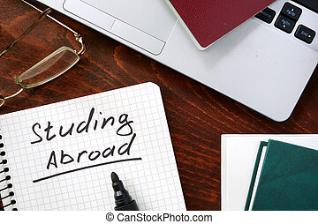 Studying Abroad  concept on a paper with notebook.