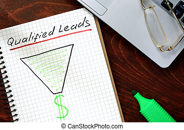 Qualified Leads  written on notebook with charts.