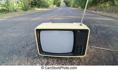 Old fashioned Tv with flickering screen on empty countryside...