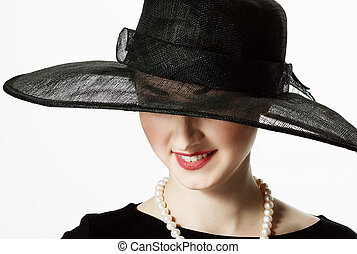 Close-up portrait of a beautiful woman in a black hat in...