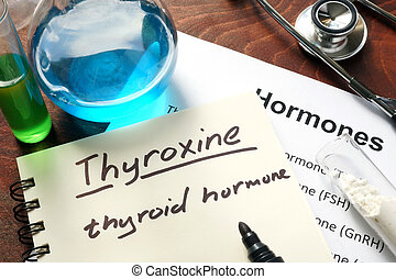 thyroxine - Hormone thyroxine written on notebook Test tubes...