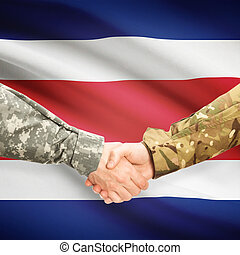 Men in uniform shaking hands with flag on background - Costa Rica