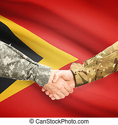 Men in uniform shaking hands with flag on background - East...
