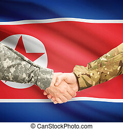 Men in uniform shaking hands with flag on background - North...