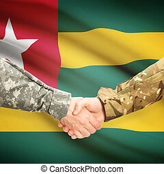 Men in uniform shaking hands with flag on background - Togo...