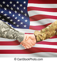 Men in uniform shaking hands with flag on background -...