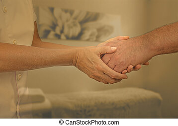 Welcoming new patient - Female therapist holding hand of...