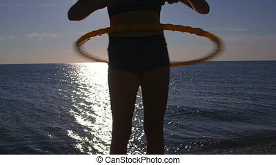 girl twirling fitness hula hoop - Young girl twirling...