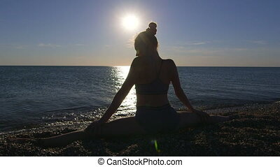 Young fit girl stretching at sunrise sitting on splits at...